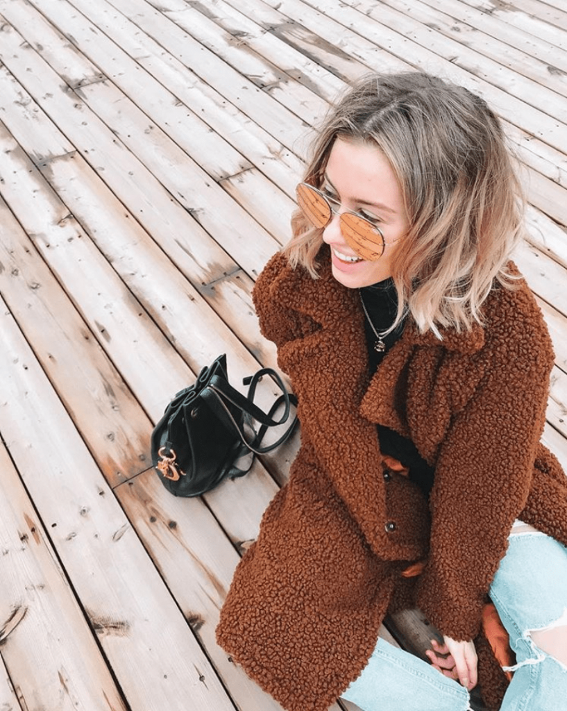 Karissa Pukas sitting on the ground in a warm brown coat