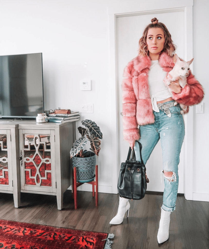 Karissa Pukas in a big pink faux fur jacket, denim and white heeled boots with a chihuahua dog