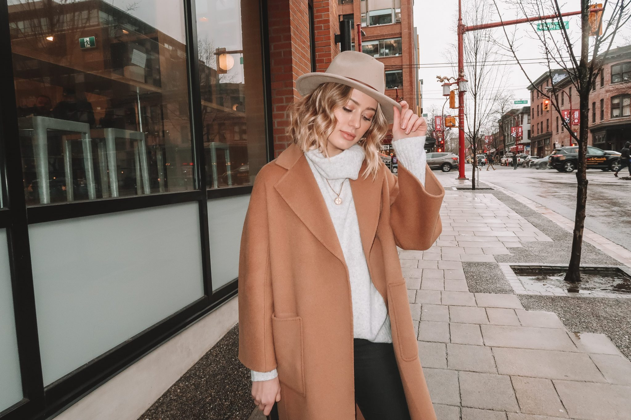 Karissa Pukas in a Camel Coat and Grey Turtleneck, tipping a grey wide brim Brixton hat