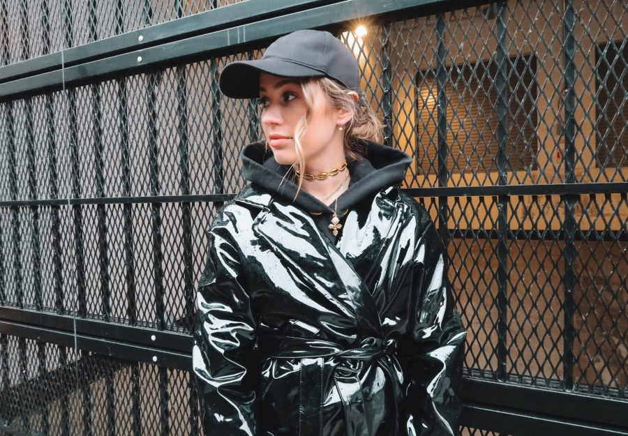 Karissa Pukas wearing a black vinyl trench coat and a black hat