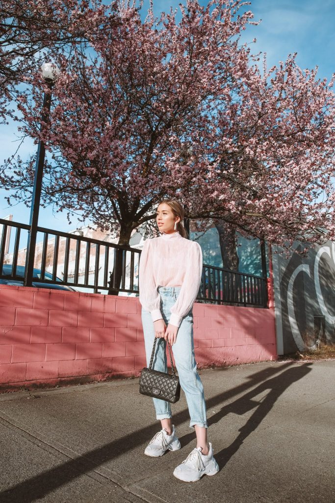 Karissa is wearing a pink puffy sleeve blouse and light wash denim, holding a chanel purse in front of Spring Cherry Blossoms.