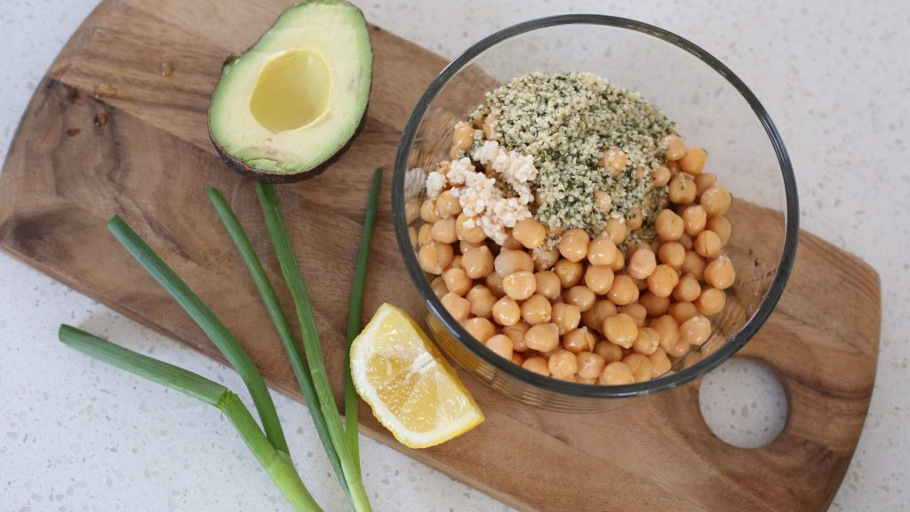 Wooden cutting board with a bowl of chickpeas on top, half an avocado, green onion and a lemon slice beside