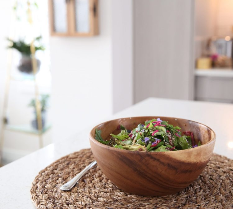 Salad in wooden bowl on kitchen island