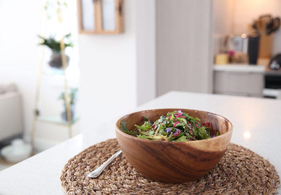 Salad in wooden bowl on kitchen island