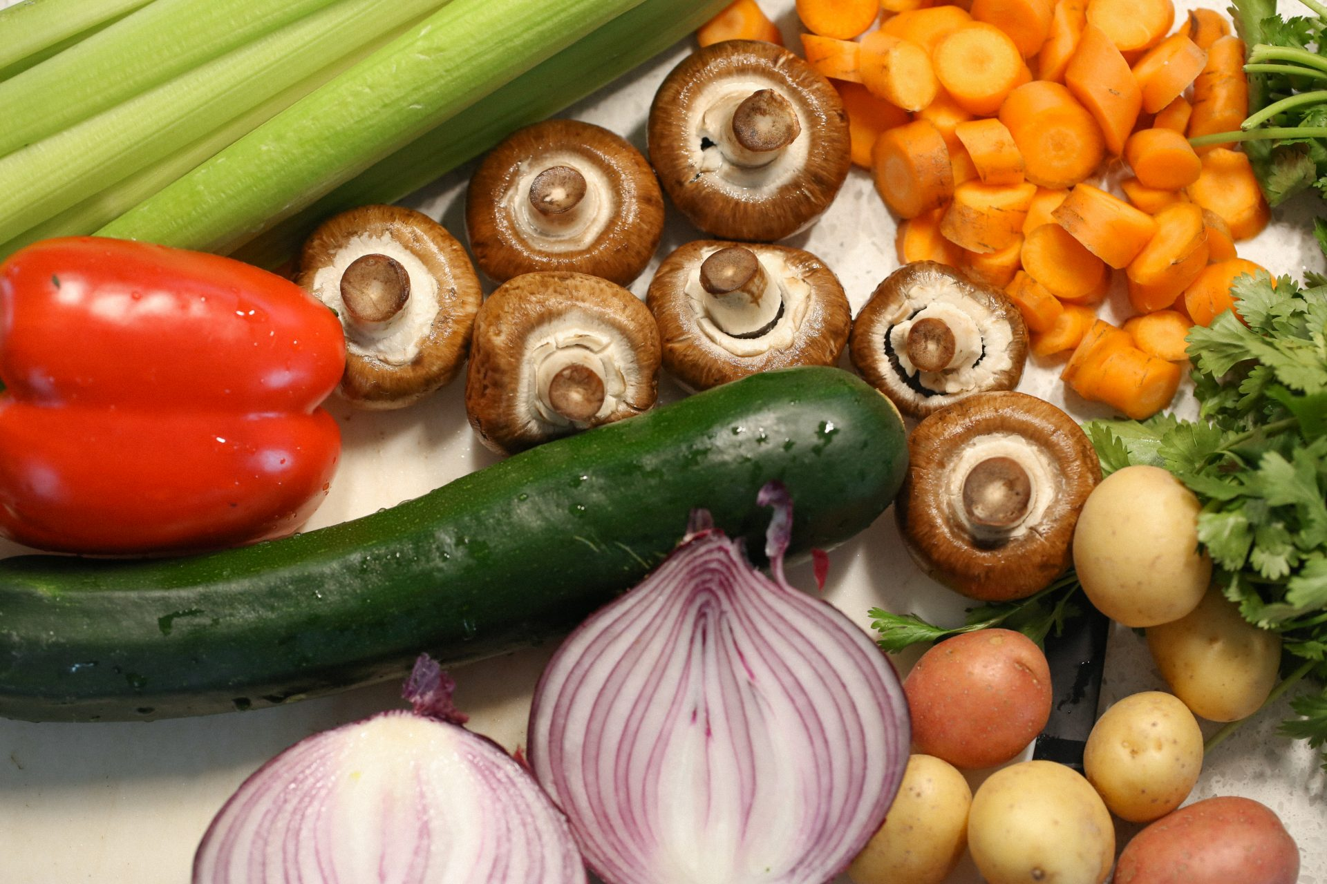 Flat Lay of vegetables, featuring red onion, potatoes, mushrooms, celery, carrots