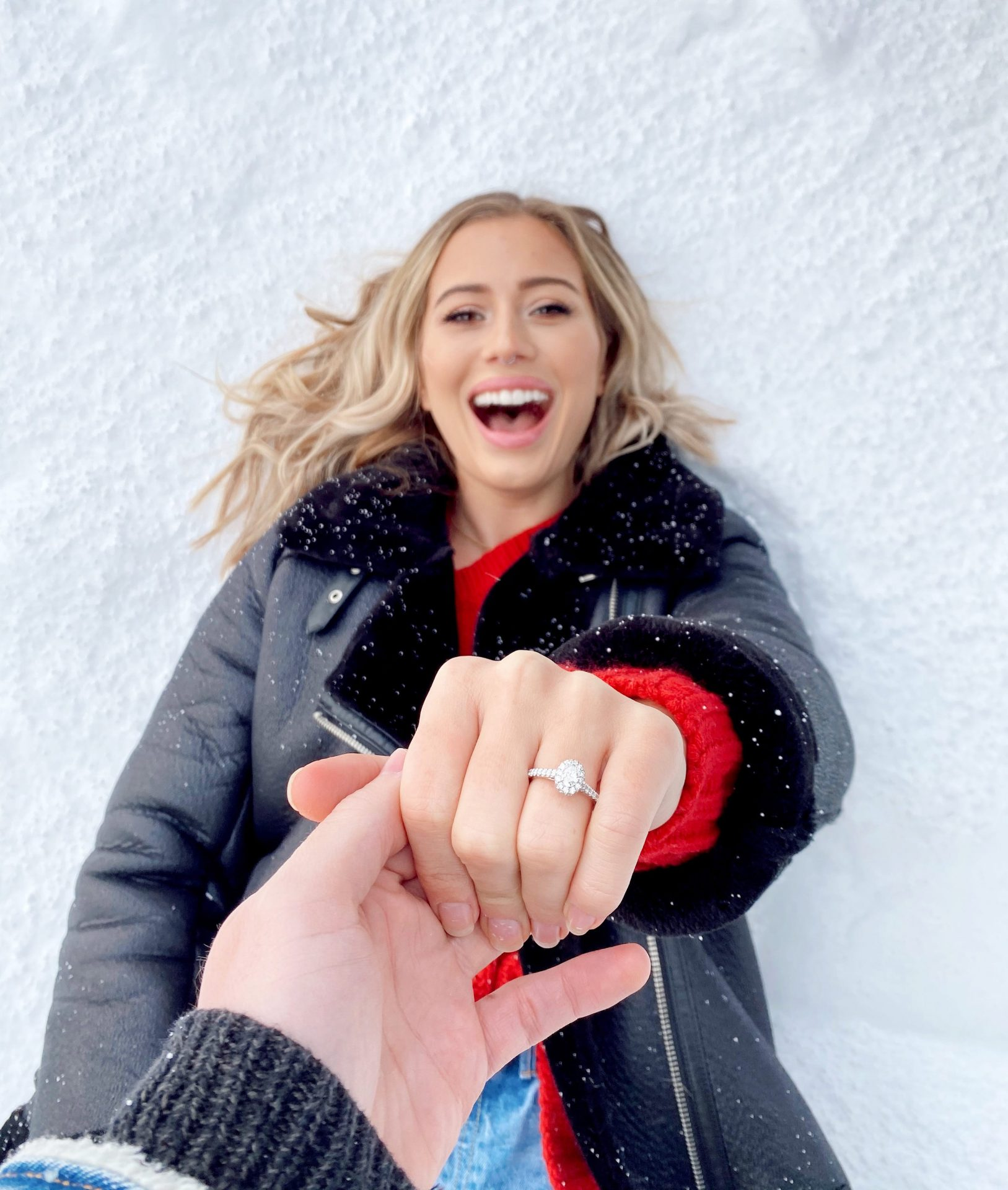 Karissa laying in the snow with Glen holding her hand towards the camera. Karissa is wearing a diamond engagement ring