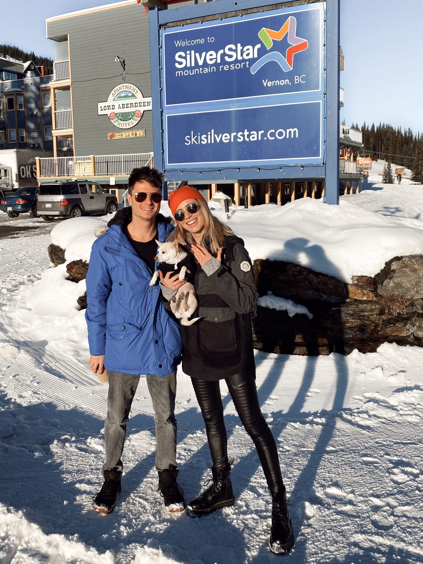 Karissa showing off her new engagement ring with Glen standing beside her. They stand in front of the Silver Star Mountain Resort sign