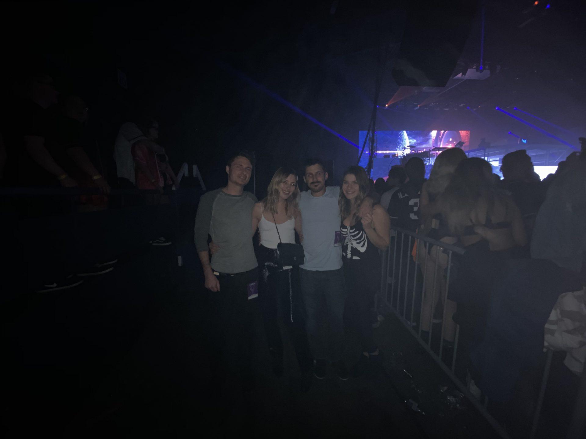 A dark image of Glen, Karissa, Justin and Katie at the Illenium show