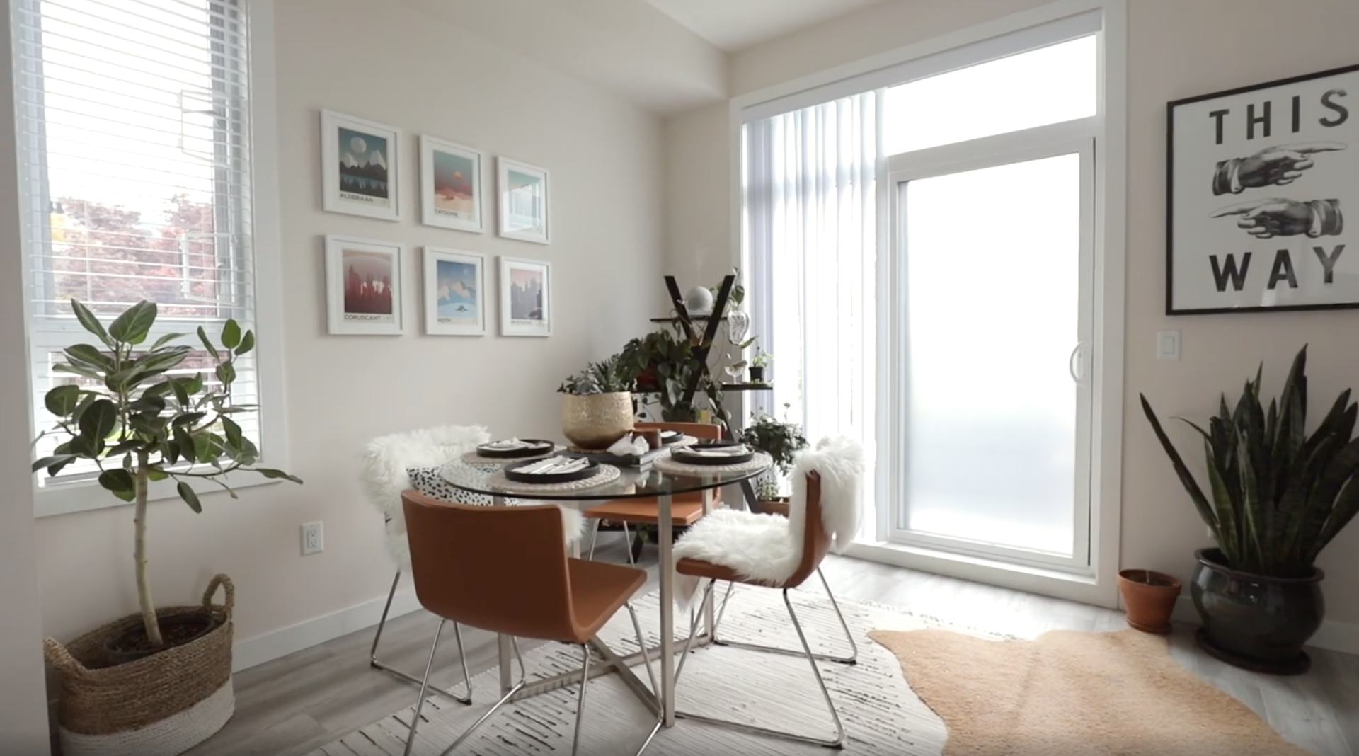 Karissa Pukas's Home Tour, Wideframe Shot of the Dining room. Large, Round Glass table with faux leather Ikea chair, plants on the floor and shelves, and artwork on the wall