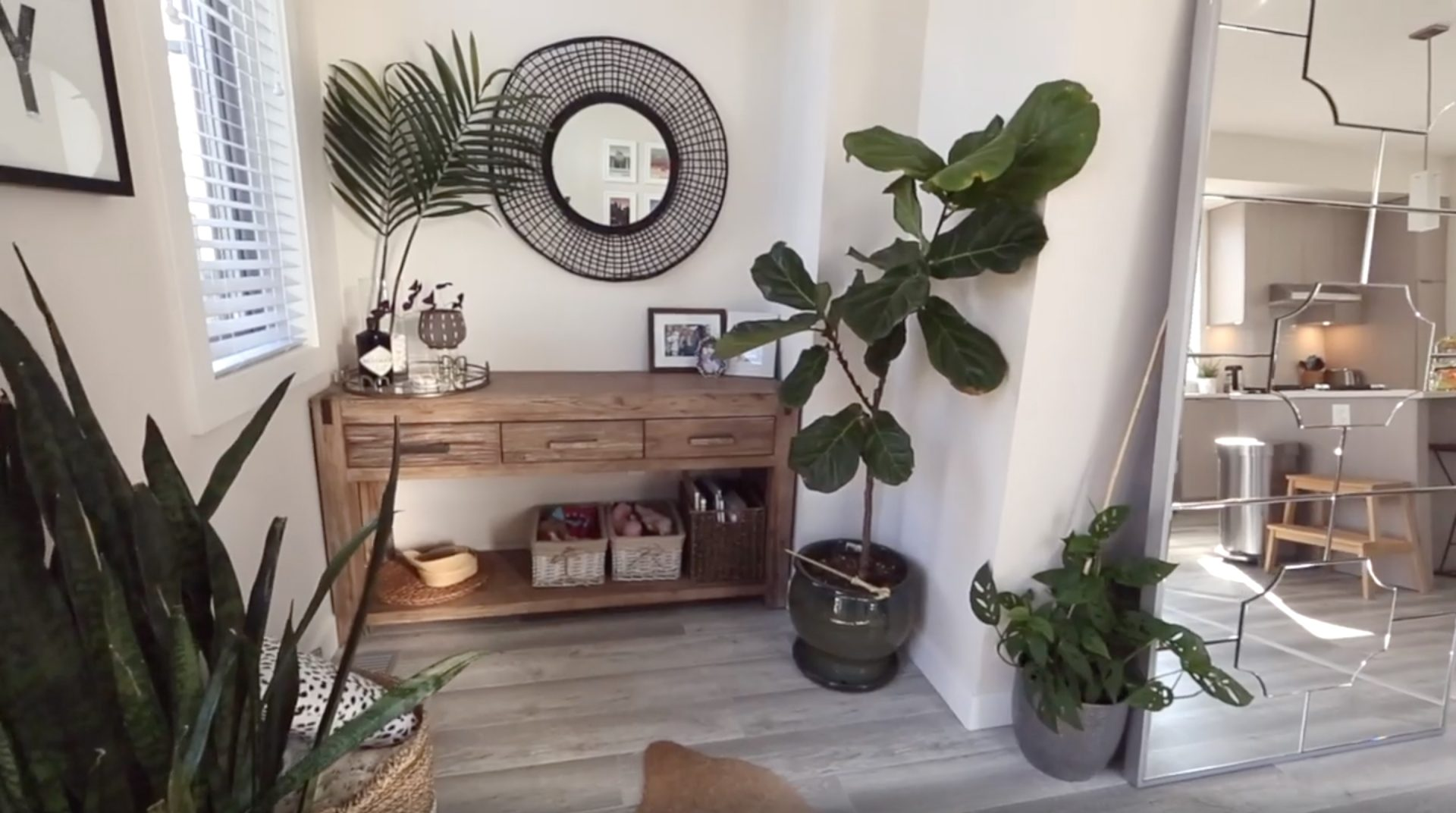 A nook in our Dining room, featuring a wooden console table with family photos, a rattan round mirror and some fake palm leaves in a vase. Large Fiddle Leaf Fig tree in the right of the frame