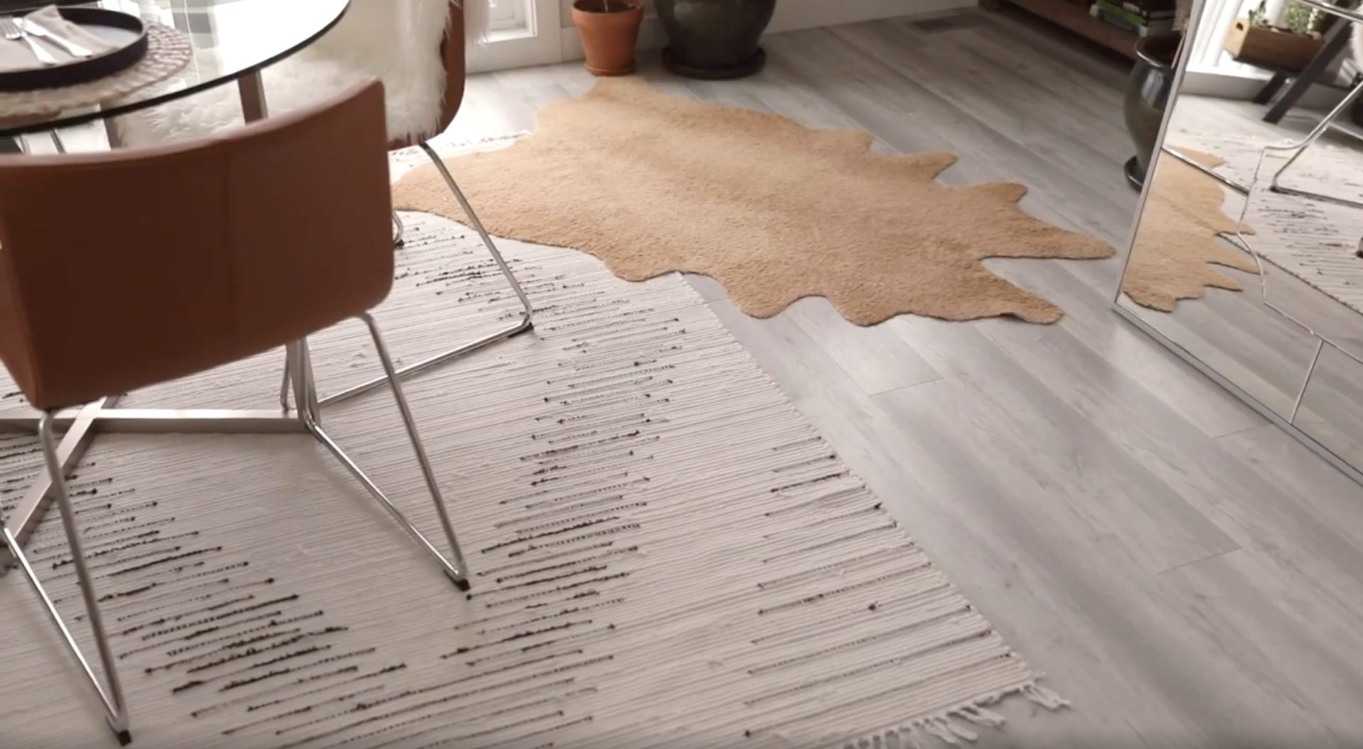 Larger white boho woven rug layered with a faux cowhide rug