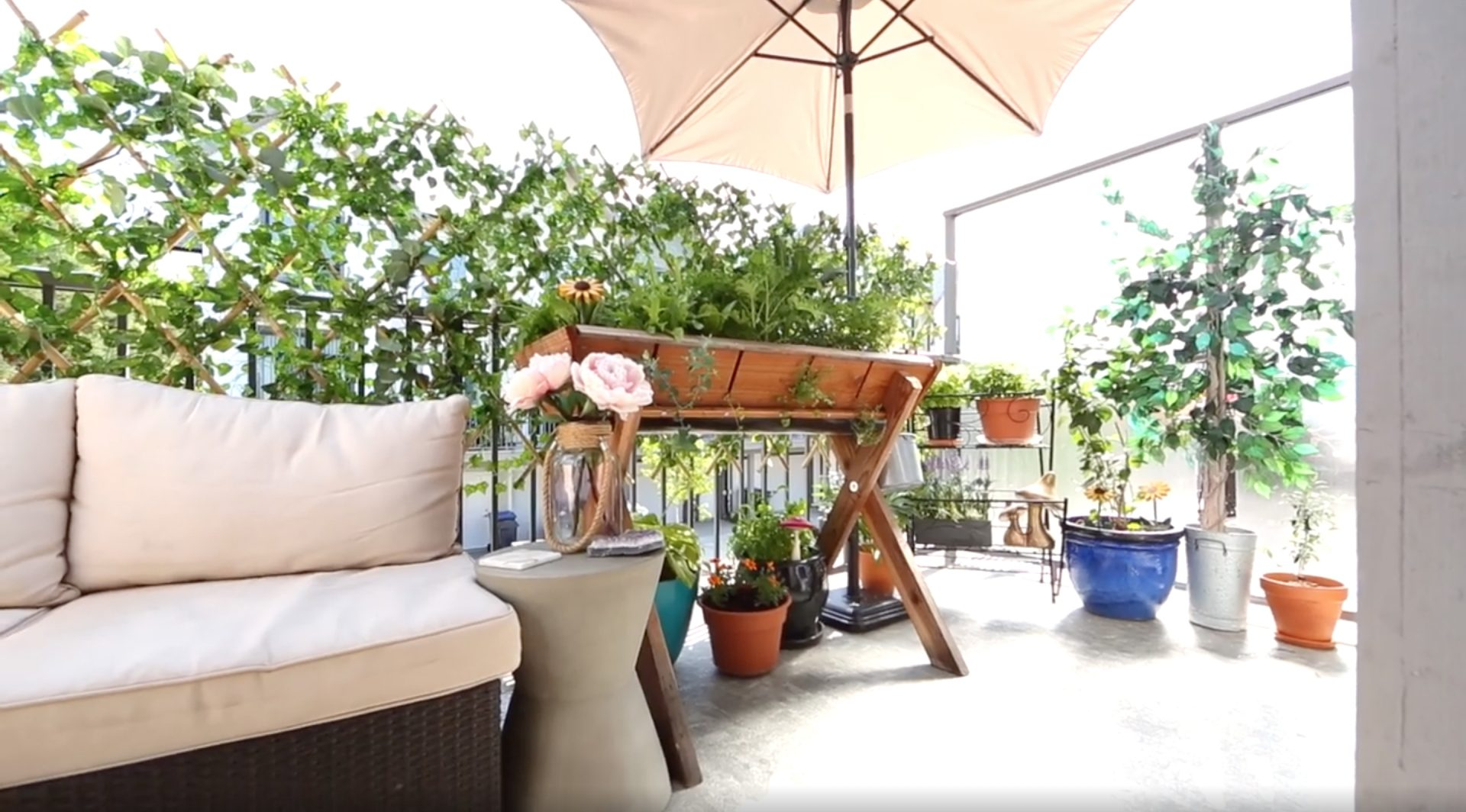 Patio in the summertime. To the left is a large sectional lounge with beige fabric cushions, middle of the frame features an above ground, wooden garden planter. There is a shade umbrella overtop of it all, and several plants to the right of the frame.