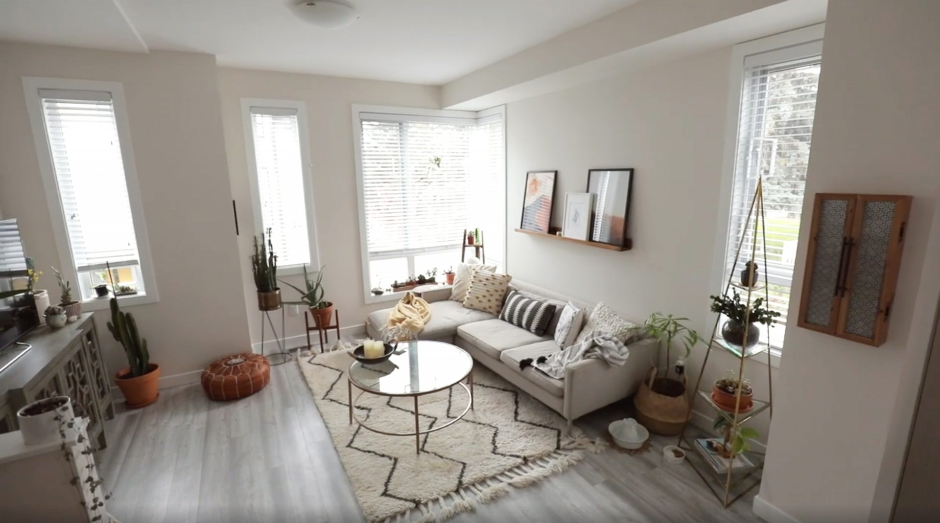Karissa Pukas's Living Room. Large cream boho rug with a bronzed gold metal round coffee table with a glass top. A large Grey L shaped couch, floating shelf and artwork on the wall. Lots of Bright Light and Windows
