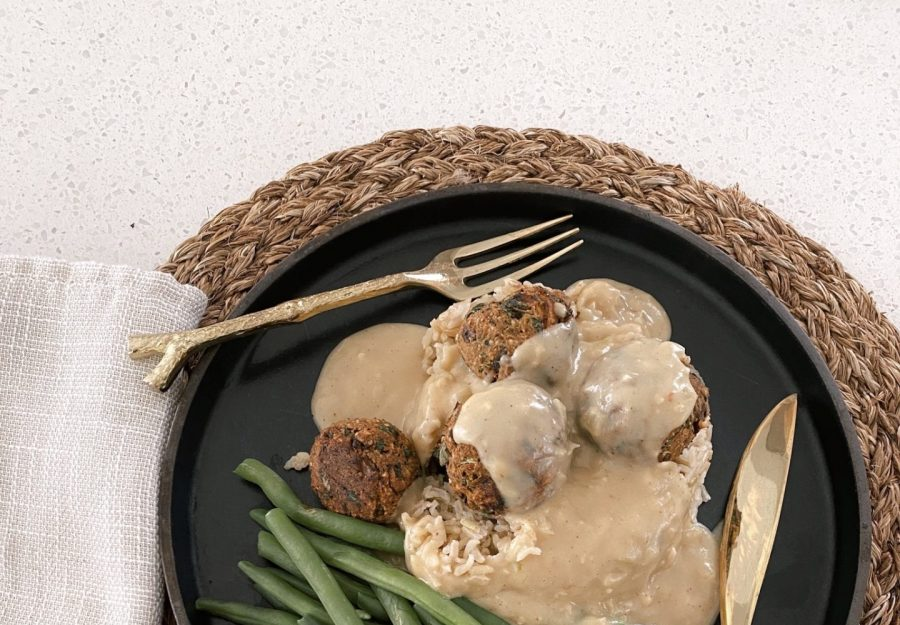 Black Ceramic plate on a placemat with plant based Swedish meatballs and green beans on top